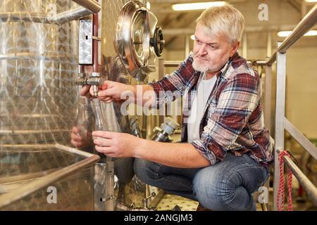 Enólogo comprueba vino fresco en el tanque de fermentación en una bodega durante el proceso de elaboración