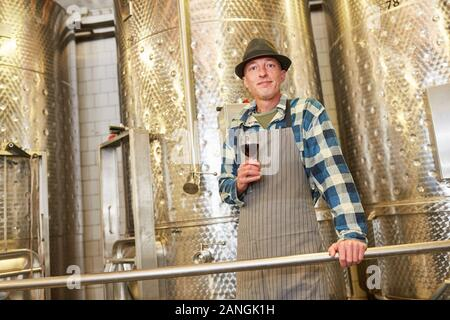 Enólogo con un vaso de vino tinto en frente de un tanque de fermentación de acero inoxidable en la fábrica.