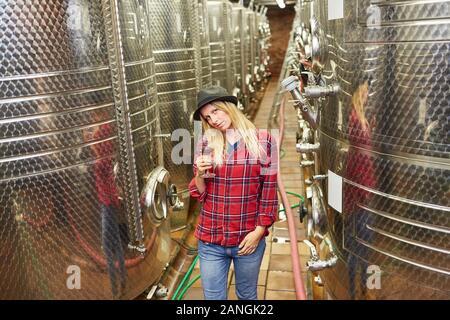 Mujer joven como un enólogo delante del tanque de fermentación de la bodega con una copa de vino tinto