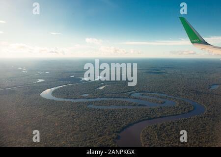 Vista del río Amazonas desde un avión, una densa selva tropical, reflejo en el agua.