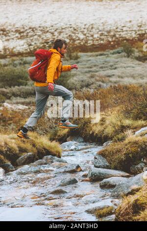 Hombre trail running cruzar el río vacaciones turismo aventura caminatas saludables en su estilo de vida activo corredor exterior con mochila en las montañas de Noruega