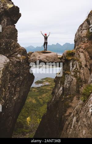 Valiente mujer viajero de pie en piedra colgante entre rocas aventura vacaciones viaje estilo de vida saludable senderismo al aire libre éxito equilibrio concepto