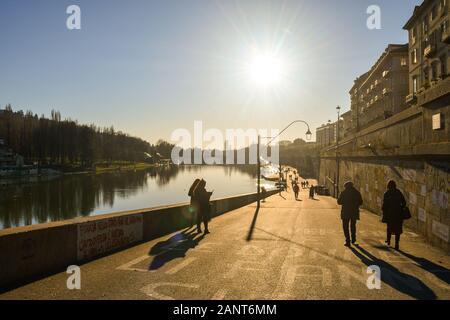Vista de la retroiluminación del Murazzi del banco del río Po con gente caminando en un soleado día de invierno en Turín, Piamonte, Italia