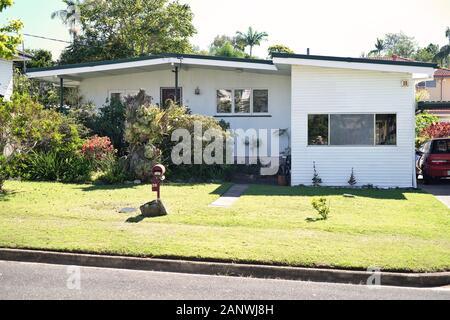 Post Guerra 50s 60s bajo establecido suburbano Casa en el suburbio de Brisbane de Carina, weatherboard con jardín de césped, puerto de coche lateral. Buzón de correo 'barril' de novedad