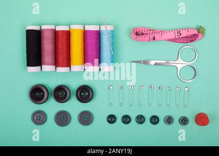 Kit de accesorios de costura.set de herramientas para la confección y coloridos hilos,agujas,pins,tijeras con fondo verde vista desde arriba.