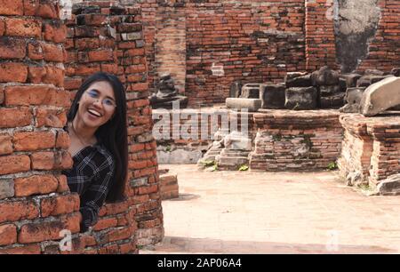 Diversión amante joven diversa niña asiática escondiéndose detrás de pared de ladrillo y sonriendo - Milennial hipster social influencer viajar a destinos turísticos culturales - viaje, tendencias y ideas de vacaciones concepto