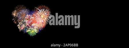 Coloridos fuegos artificiales en la forma de un corazón panorámica sobre fondo negro. Día de San Valentín banner web.