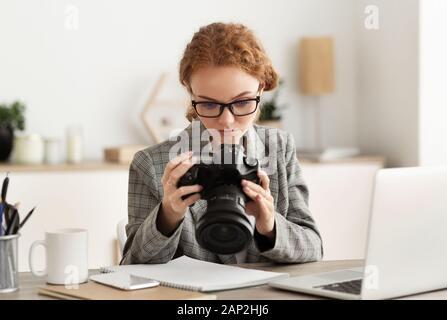 Joven fotógrafo procesar las imágenes en el ordenador portátil, mirando photocamera