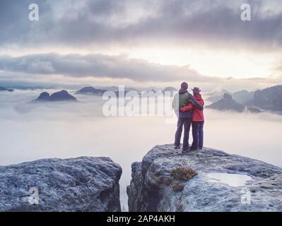 Pareja feliz con disfrutar de la vista después de subir la parte superior de la montaña rocosa. Socios ver la belleza de la naturaleza salvaje en la montaña de madera