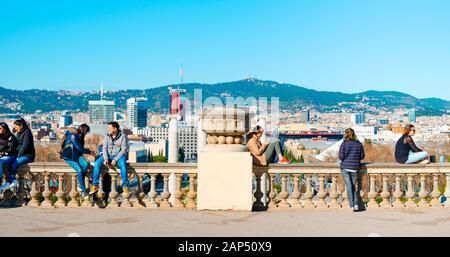 BARCELONA, España - 18 de enero de 2020: Gente colgando en la parte superior de la ladera de Montjuïc en Barcelona, España, con la ciudad debajo de ellos y la montaña del Tibidabo