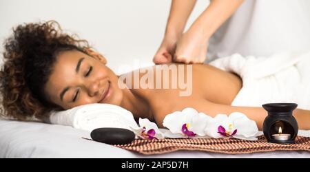 Mujer negra disfrutando de un masaje con velas y flores cerca