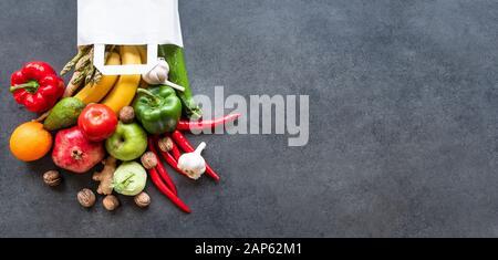 Selección de alimentos saludables: frutas, verduras, semillas, súper alimento vegetal, la hoja de antecedentes de cemento gris en una bolsa de compras.