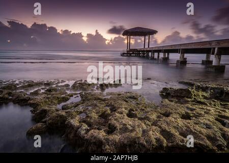 Cenador en el muelle con olas brumosas rompiendo en la costa rocosa, Grand Cayman Island