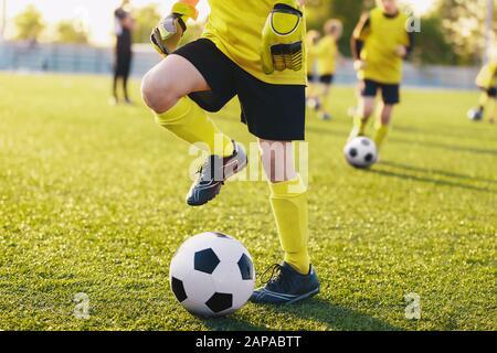 Jugadores de fútbol en el campo de entrenamiento en el campo de fútbol. Los niños practican el fútbol el día de verano. Los niños participan en un campamento deportivo para jóvenes talentosos que practican el fútbol