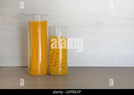 Pasta en recipientes grandes de vidrio de tarros de pie sobre mesa gris en la cocina. Pasta italiana cruda con espaguetis.