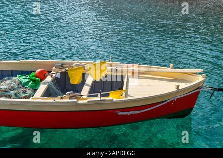 Parte de un pequeño barco de pesca pintado en rojo brillante, beige y verde en el agua azul de la costa mediterránea en un día soleado. Hay padd