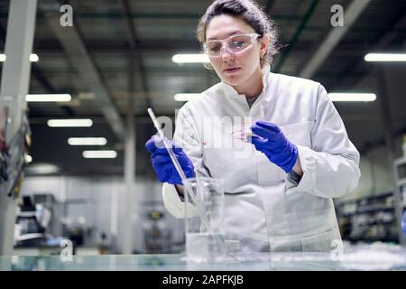 Una joven mujer seria de laboratorio en vasos y en el plato de Petri en sus manos lleva a cabo experimentos sobre el fondo desenfocado