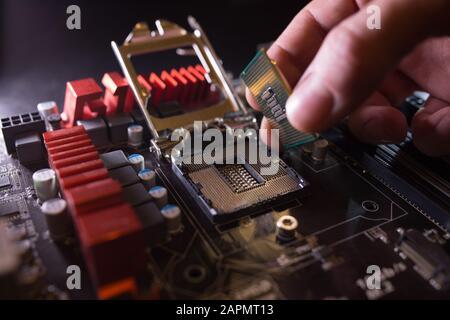 El técnico conecta el microprocesador de la CPU al zócalo de la placa base. Antecedentes del taller. Concepto de actualización o reparación de PC.