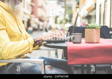 Hombre de negocios de moda usando portátil en el bar cafetería al aire libre - Mature hipster masculino navegando en línea y bebiendo café - Tecnología y estilo de vida de moda
