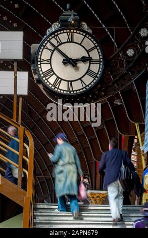 Los pasajeros escalan a pasos del puente peatonal en la estación de tren de York con un gran reloj de estación y estructura de techo arriba.