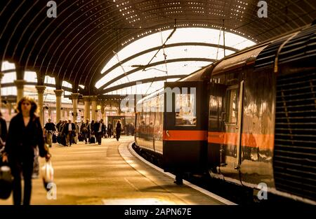 Pasajeros y tren en la plataforma de la estación de ferrocarril de York, Reino Unido.