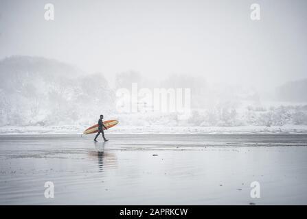 Surfista caminando por la playa en Maine durante una tormenta de nieve en invierno