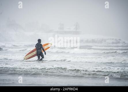 Surfista caminando hacia las olas durante una tormenta de nieve en Maine