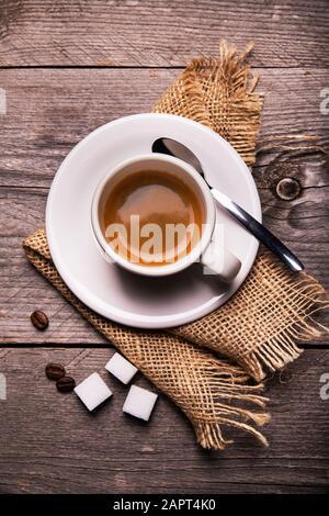 en la mesa rústica de madera, en primer plano, con vistas desde la parte superior, una taza de café espresso cremoso. Composición vertical