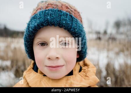 retrato de un niño mirando mientras juega fuera en invierno
