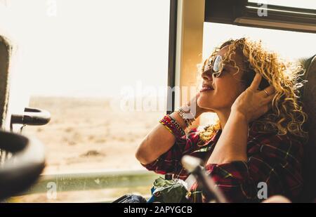 Hermosa mujer adulta rubia disfrutando del viaje en autobús o tren escuchar música con auriculares - estilo de vida wanderlust y feliz gente haciendo viaje -