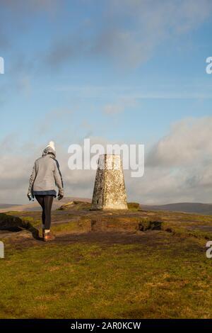 Mujer caminando hasta el punto de triangulación punto trig en la colina de Shutlingsloe en el distrito de los picos ingleses