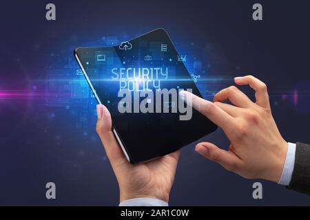 Hombre de negocios que sostiene un smartphone plegable con inscripción EN LA POLÍTICA DE SEGURIDAD, concepto de ciberseguridad
