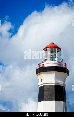 Tiro vertical de ángulo bajo de un faro bajo la hermosa nube en el cielo Foto de stock