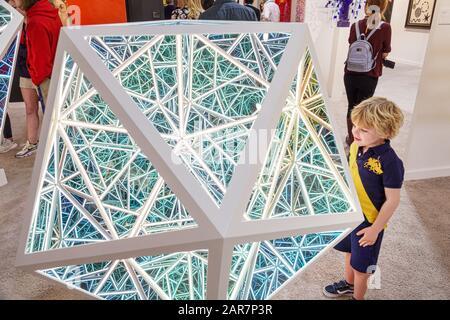 Florida Miami Art Basel Art Miami exposición interior galería Anthony James Neon escultura niño mirando espejos de espejo infinito