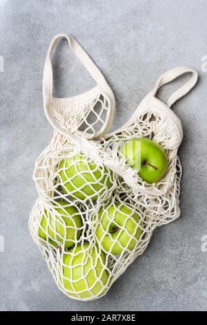 Bolsa de malla con manzanas verdes sobre fondo de hormigón gris. Vista superior. Concepto de cero residuos, concepto de estilo de vida ecológico saludable