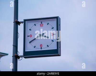 Reloj de calle con un dial tradicional y flechas de manos durante horas y minutos. Un reloj analógico rectangular en caja en un poste de iluminación de la ciudad muestra el exacto