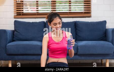 Una joven asiática se toma un descanso después de entrenar y beber agua después de hacer ejercicio en la sala de estar