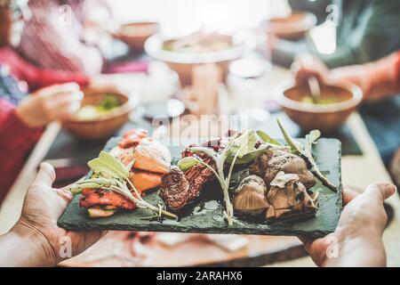 Chef mujer que sirve tomates secos, alcachofas cocinadas, pimientos dentro de un restaurante gourmet vegetariano - Feliz gente mayor comiendo y bebiendo