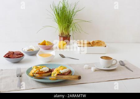 Huevos Benedict, muffins ingleses, jamón a la parrilla, huevos escalfados, salsa holandesa, hierbas de cebolleta, limón, taza de café. Mesa de madera blanca con desayuno.
