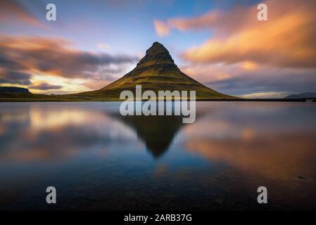 Puesta de sol sobre la montaña Kirkjufell con reflexión en un lago cercano en Islandia Foto de stock
