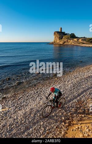 Biker de montaña moviéndose en el camino de la playa costera; Playa el Charco; Pueblo Villajoyosa; Provincia de Alicante; España