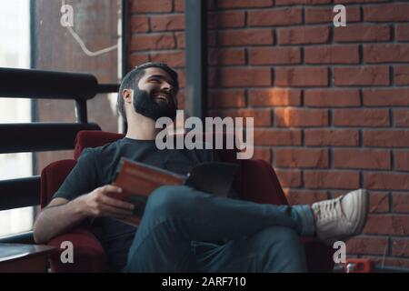 Retrato apuesto hombre barbado vistiendo ropa informal. Hombre sentado en la silla roja loft moderno studio, leyendo cómics y relajante