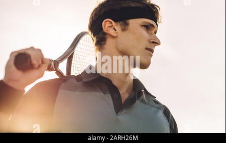 Primer plano de un jugador de tenis profesional que se encuentra fuera en un día soleado. Jugador de tenis masculino con raqueta mirando lejos.