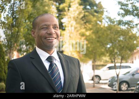 Hombre de negocios negro en un traje que parece exitoso en un fondo urbano