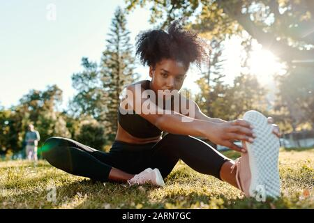 Retrato de una mujer joven afroamericana determinada sentada en hierba verde por la mañana, la luz del sol estirando las piernas mirando a la cámara
