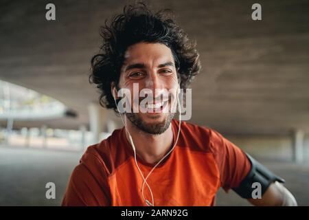 Retrato de un joven corredor masculino feliz con auriculares en sus orejas mirando a la cámara al aire libre sonriendo - ajuste excitado masculino