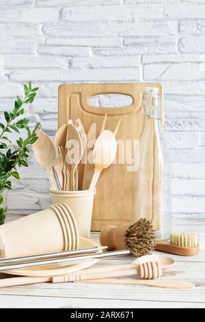 utensilios ecológicos sobre fondo de madera sobre pared de ladrillo blanco. . Vajilla, cepillos, cucharas y botellas. Concepto de cero residuos.