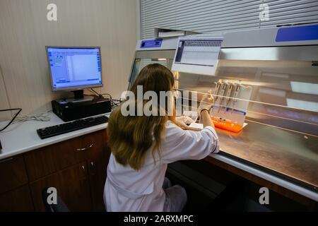 Trabajo científico en caja laminar. Pone muestras de fragmentos de ADN para electroforesis