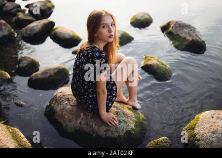 Mujer con vestido negro sentado en roca en el mar