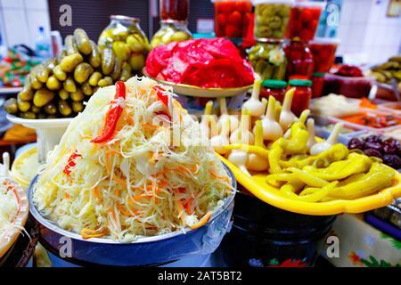 Verduras encurtidas, ensalada de colina con chucrut, zanahorias y pimientos dulces sobre el fondo de otras verduras fermentadas en el borrosidad.